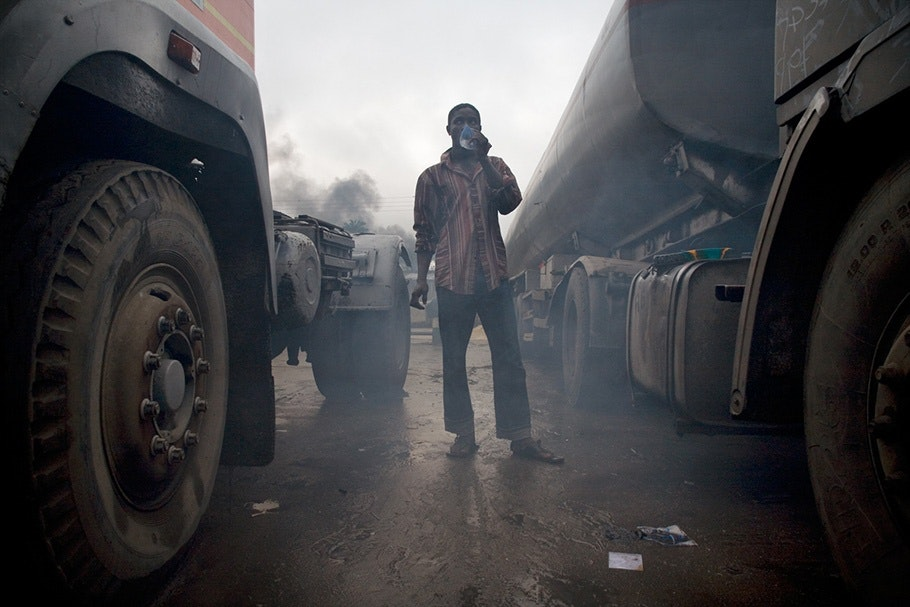 Man between trucks with smog.