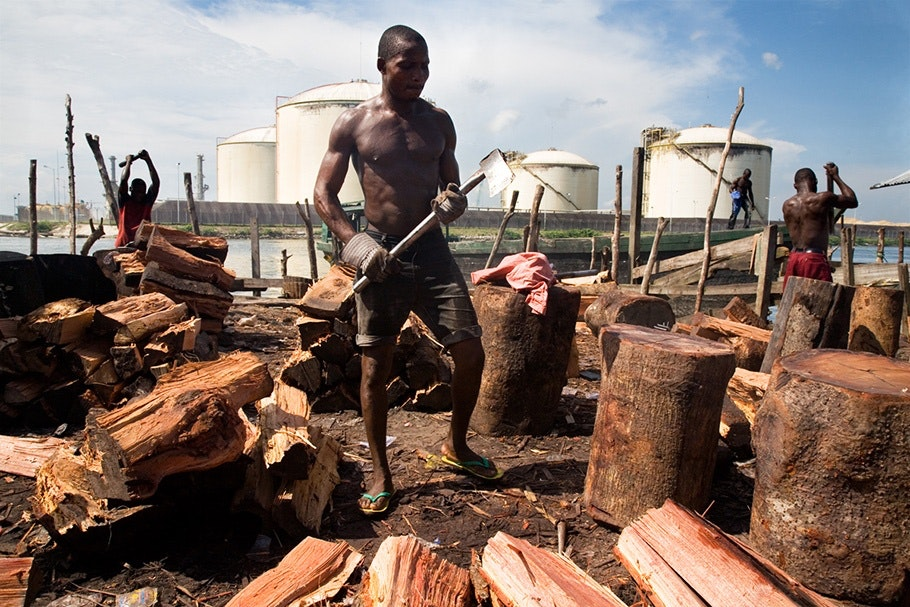 Man chopping wood in front of tanks.