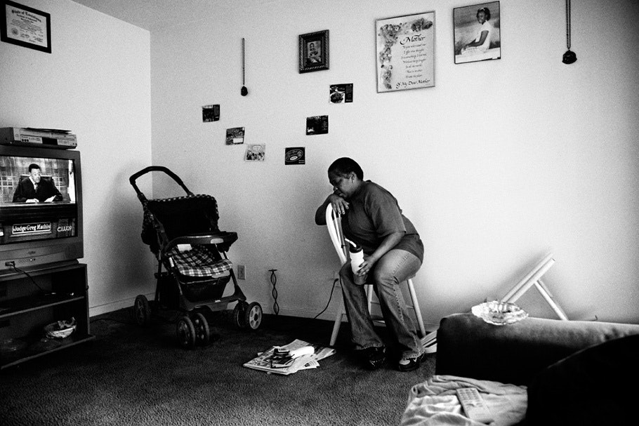 Woman sits in chair; stroller in corner