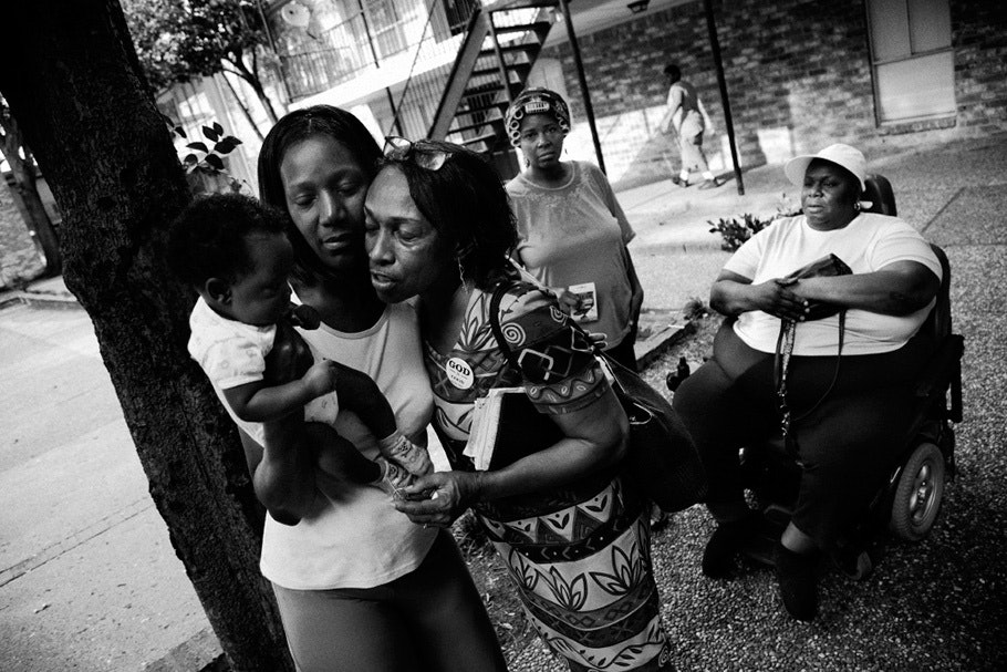 Women hugging with baby in foreground, wheelchair in background.