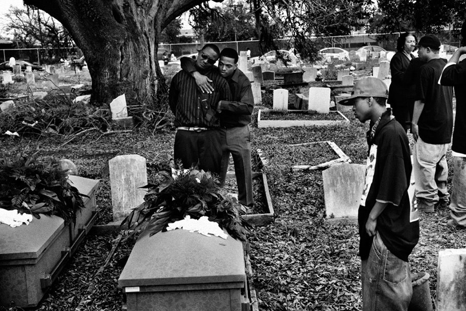 Men embracing in cemetery.