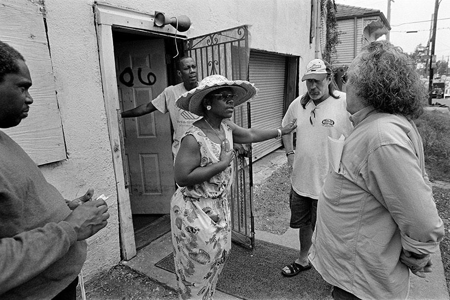 Group of people; woman in hat in front of door.