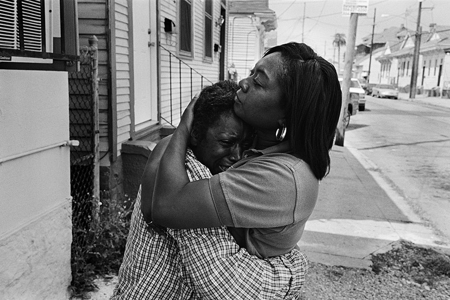 Two people embracing outside a home.