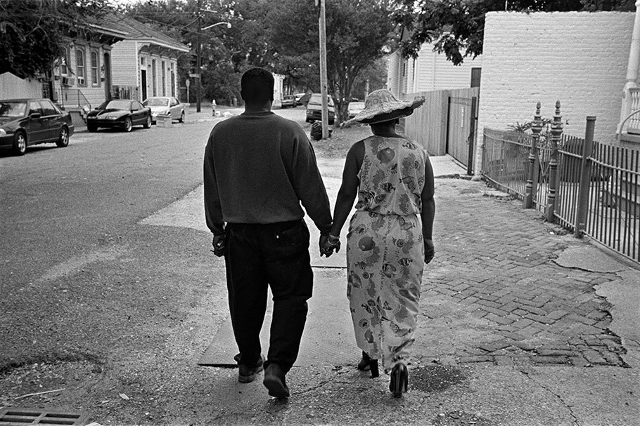 Couple holding hands, viewed from behind.