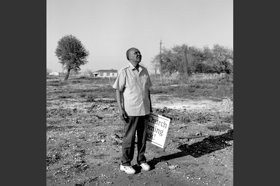 Man holding church sign, looking up