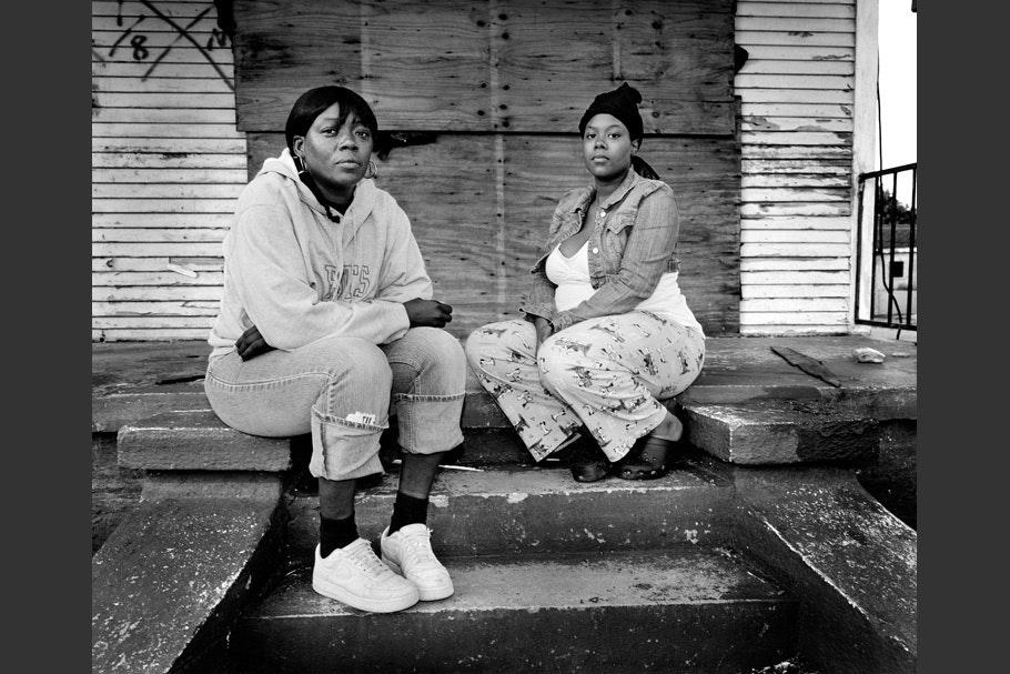 Two women sitting on steps.