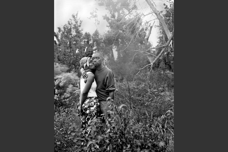 Couple standing among plants and trees.