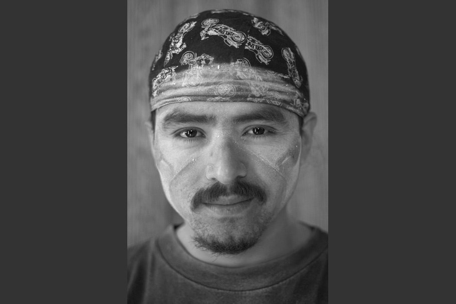 Man wearing bandana, with dust on face.