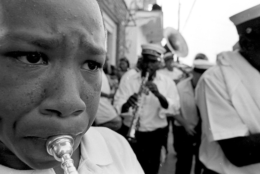 Close up of horn player, band in background.