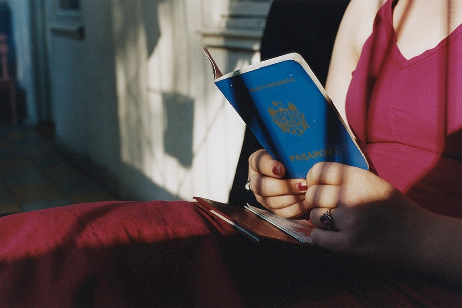 Woman in pink holding passport.