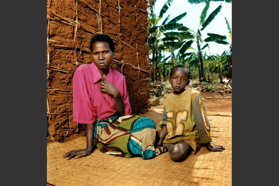 Boy sits on ground next to mother