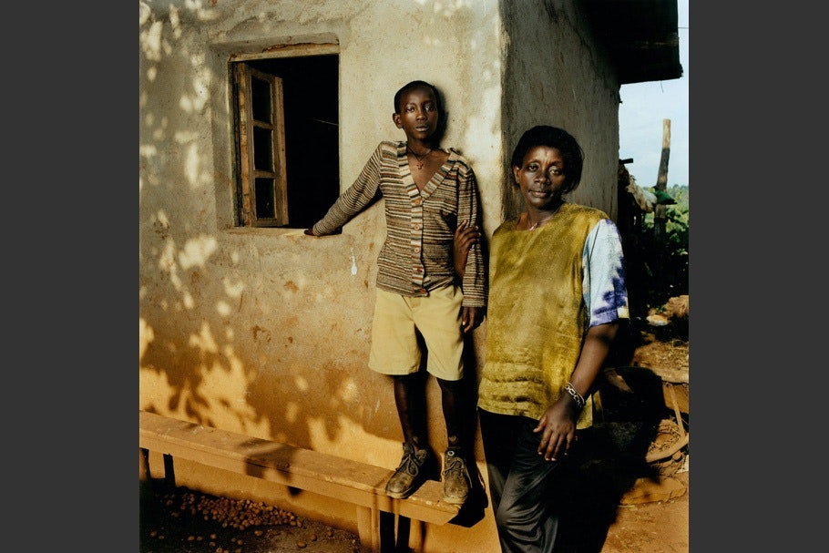 Standing in front of home with window, child standing on bench, striped shirt, mother in tan vest.