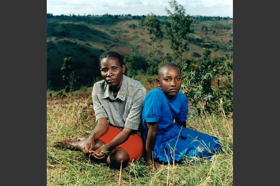 Mother and daughter sit in grass