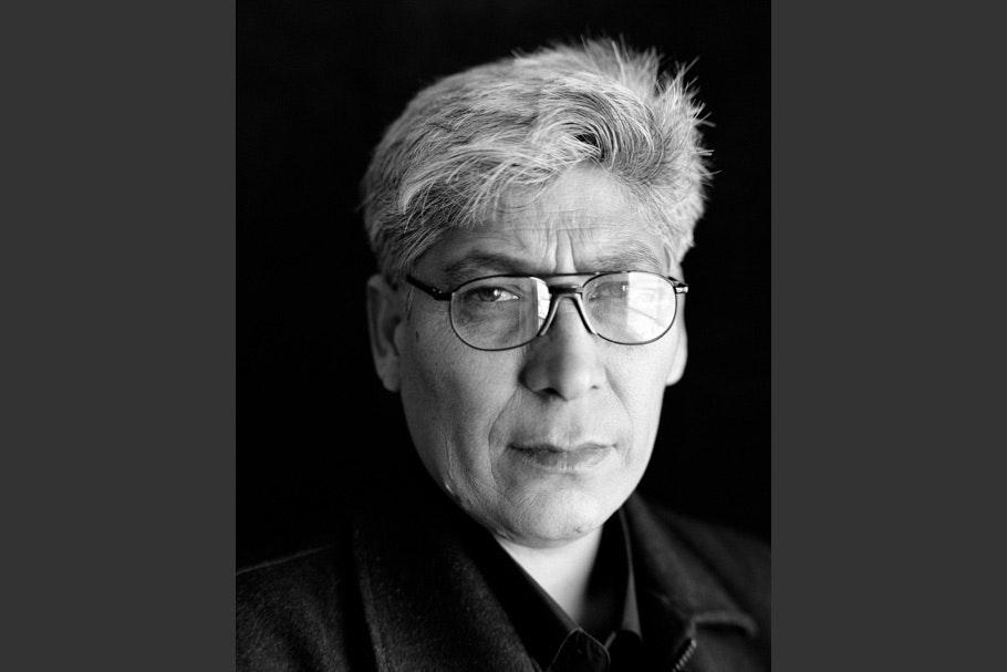 Man with gray hair, glasses, dark shirt, no tie.