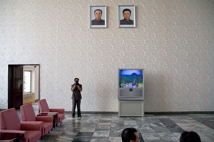 Man standing with two portraits above, red chairs, tv.