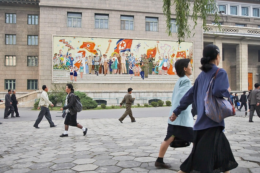 People walking by a mural.