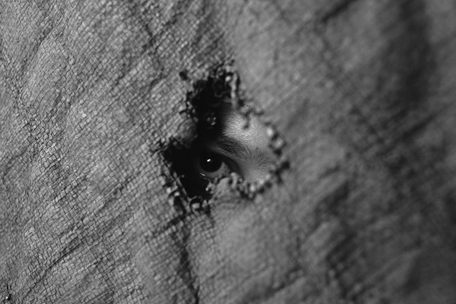 Eye peering through fabric.