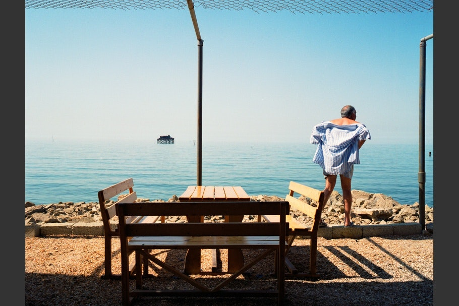 Man and table in front of water, blue shirt.