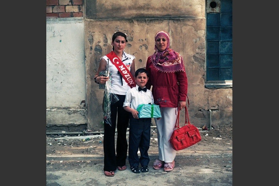 Girl with rose stands next to boy and mother.