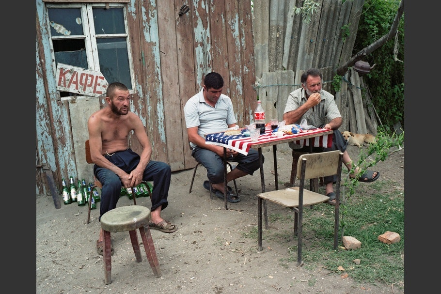 Three men sitting at a table with an American flag on it.