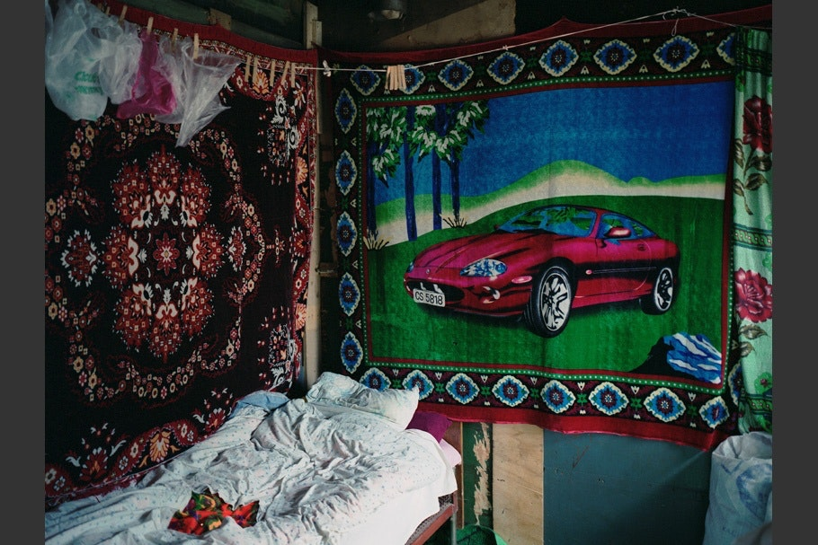Bed and hanging rugs in railway car.