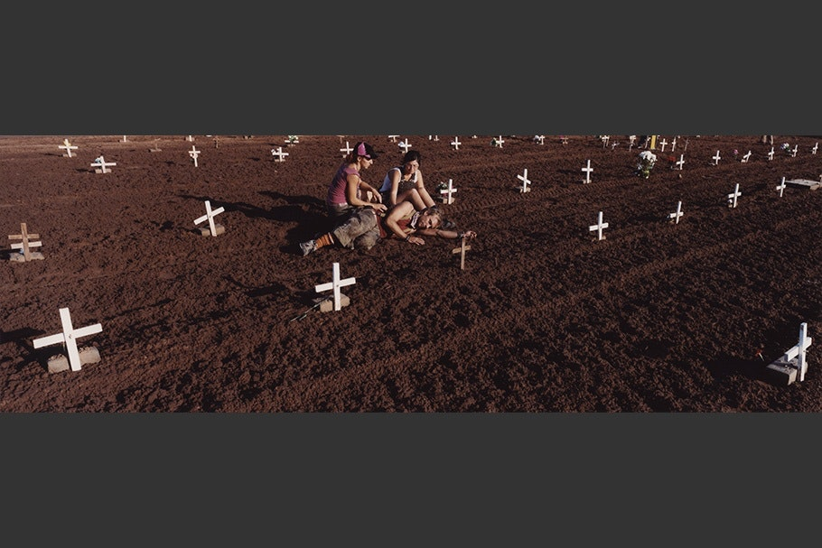 People in cemetery with white crosses.