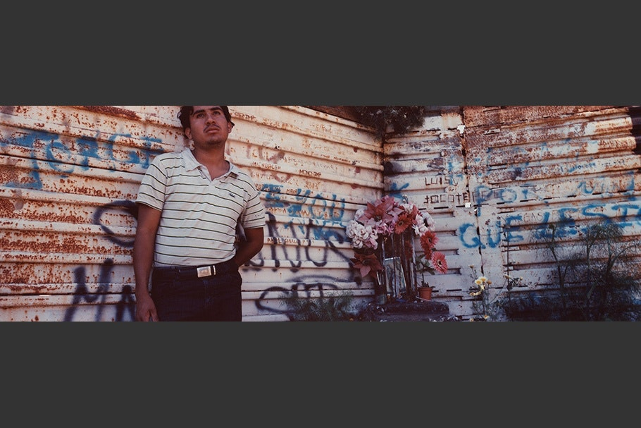 Man in front of wall with graffiti.