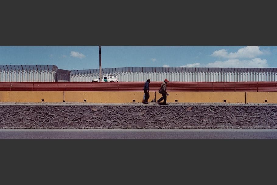 Two men walking along the border.