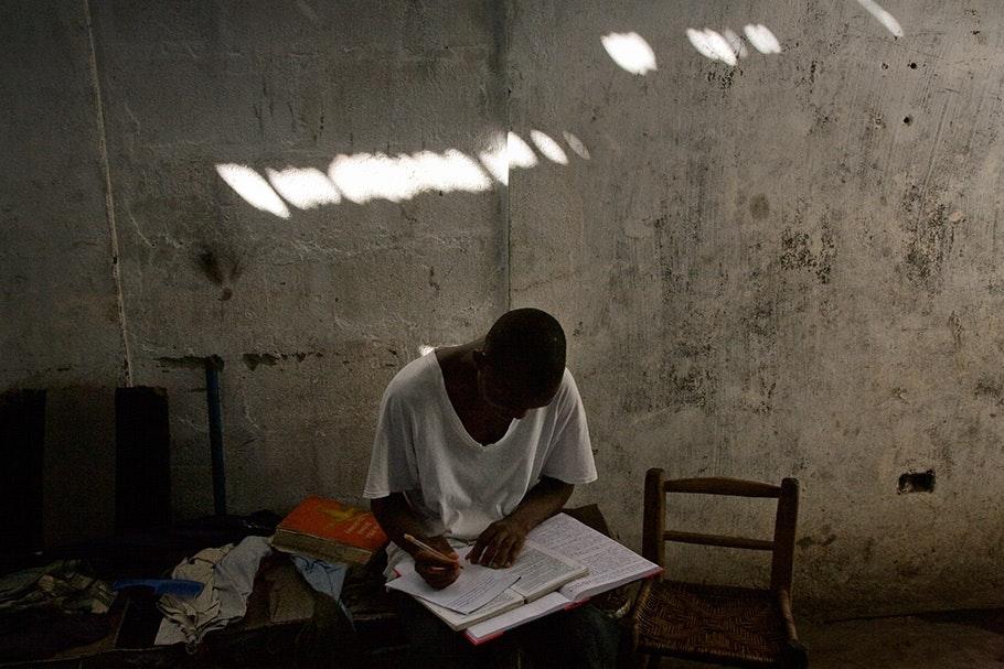 Boy at desk, light across wall.