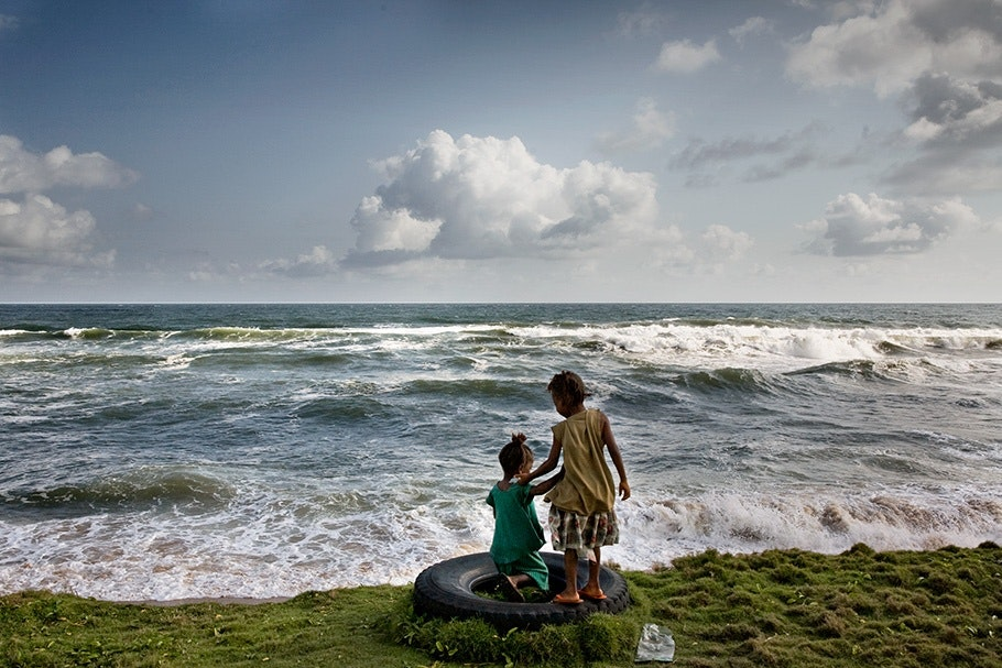 Children playing on tire in front of ocean.