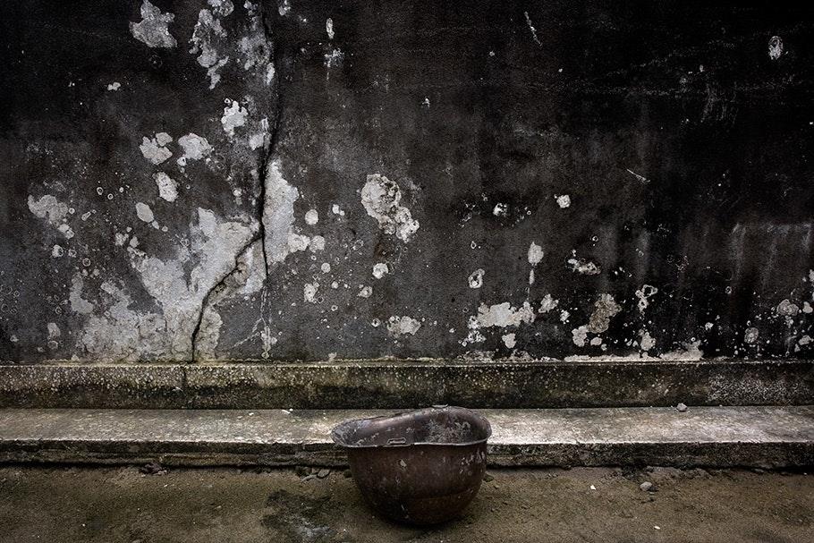 Helmet on ground, gray wall.
