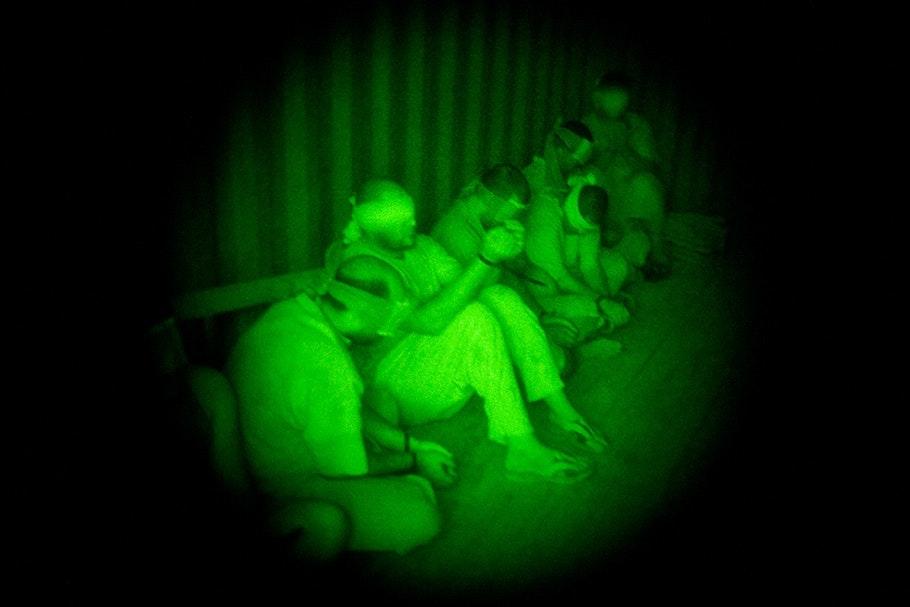 Row of blindfolded men. Green.