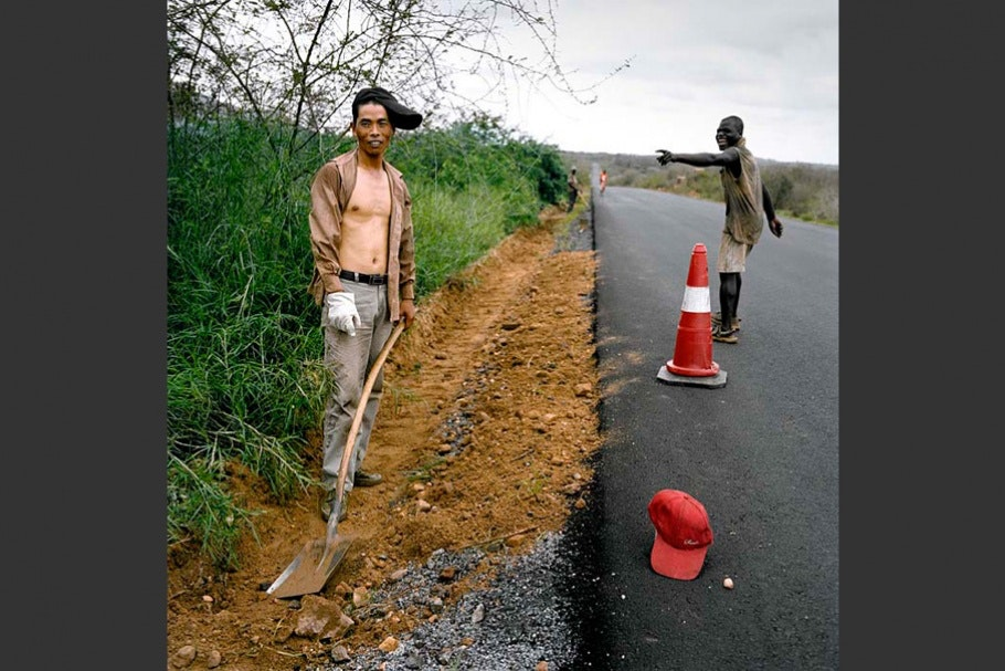 Men on road with traffic cone.