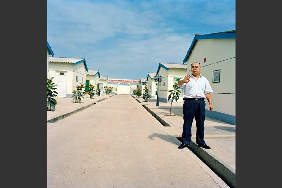 Man on street with white houses.