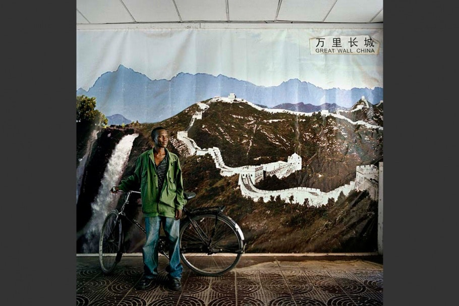 Man with bicycle in front of mountain mural.