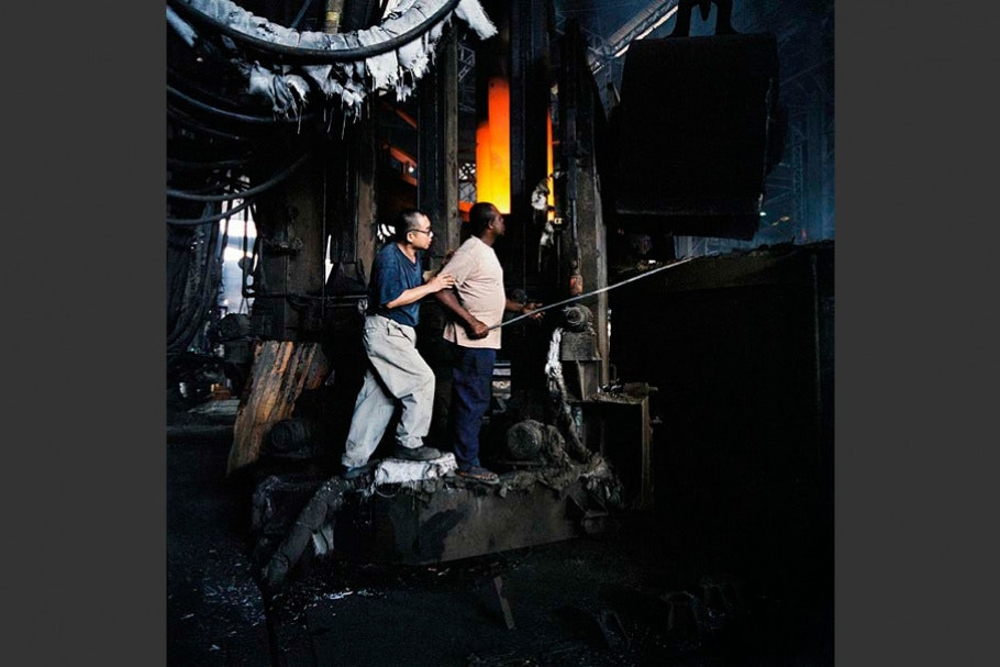 Two men working in factory setting.
