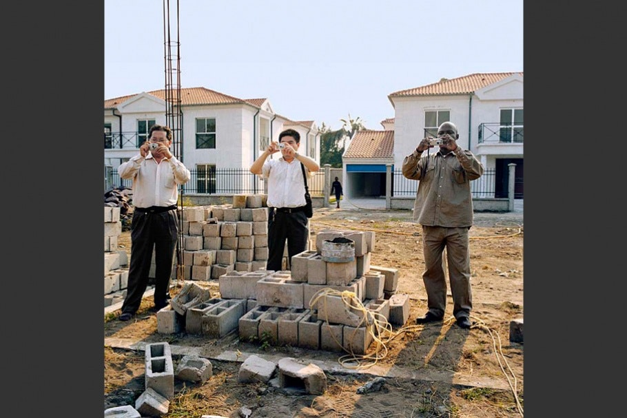 Three men photographing a construction site.