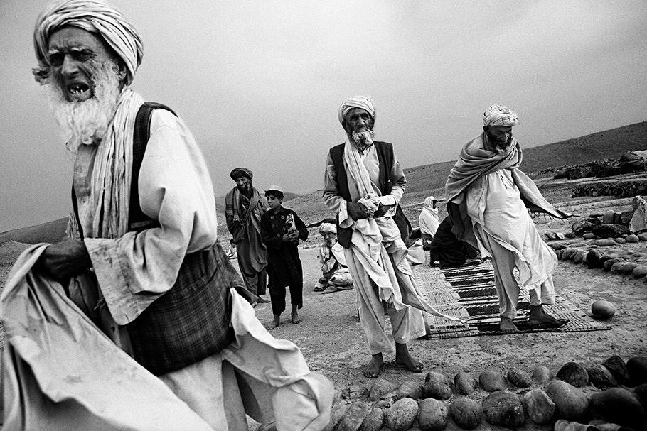 iagonal horizon, man in turban in foreground, more behind him.