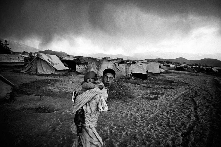 Man with child on back, tents in background.