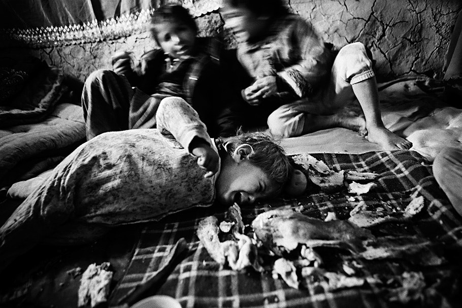 Child lying on floor, two more in background.