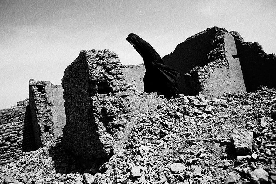Woman in black walking through ruined building.