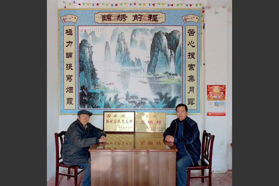 Two men facing each other at desk, large poster on wall.