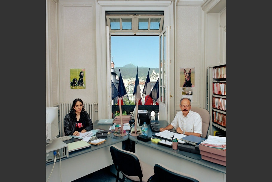 Two desks, open window with French flags.