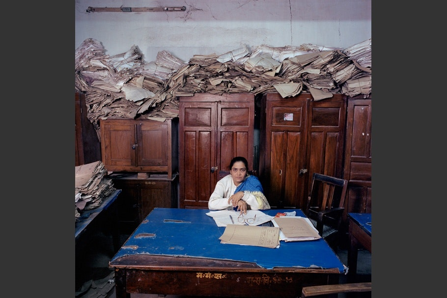 Piles of paper behind woman at desk.