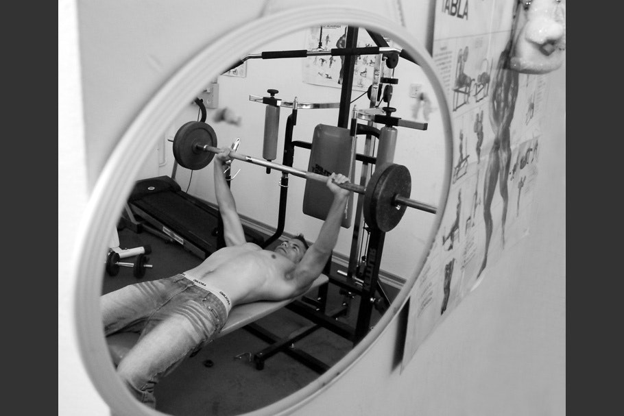 Weight lifting seen through mirror.