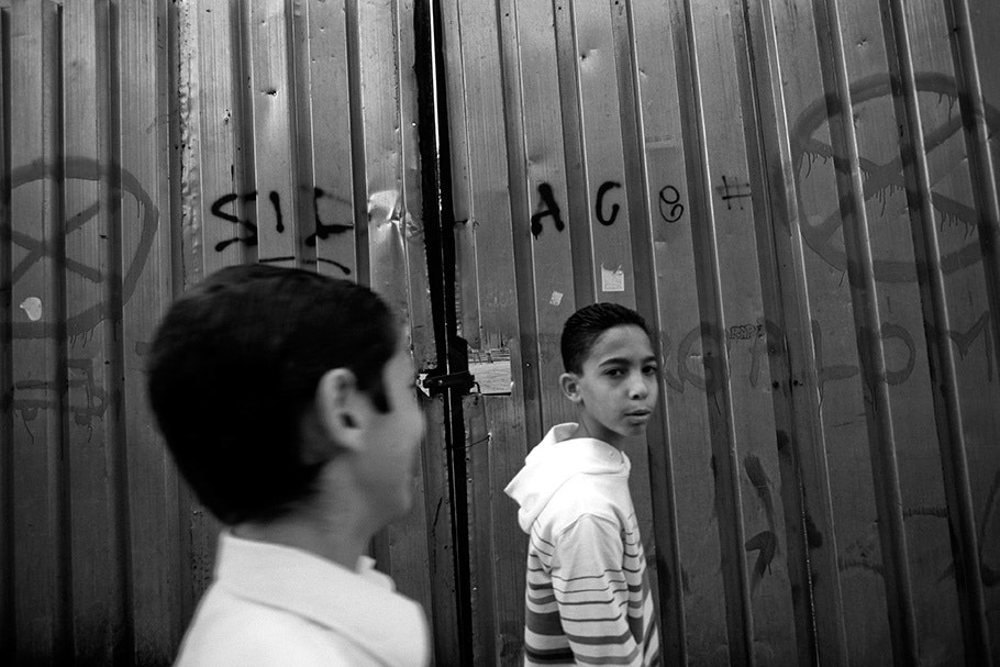 Boys in front of fence with graffiti.