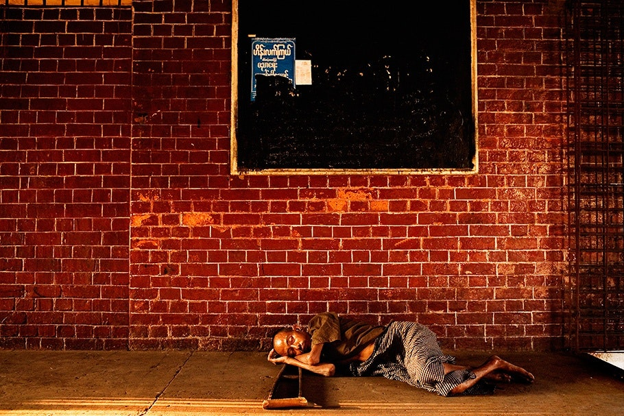 Man sleeping in front of a brick wall.