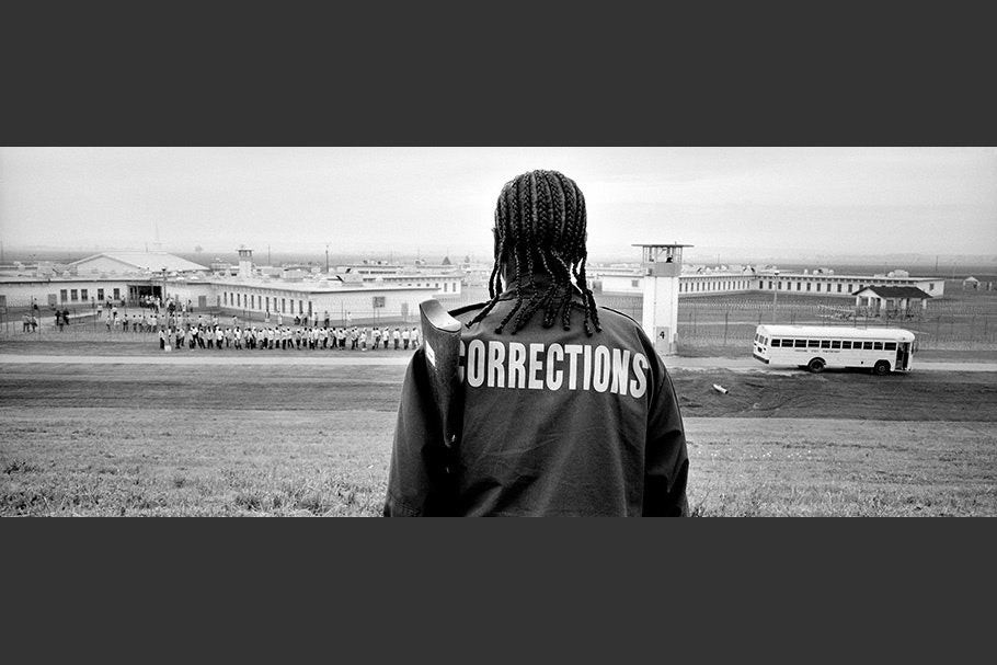 """Back of man with """"corrections"""" jacket."""