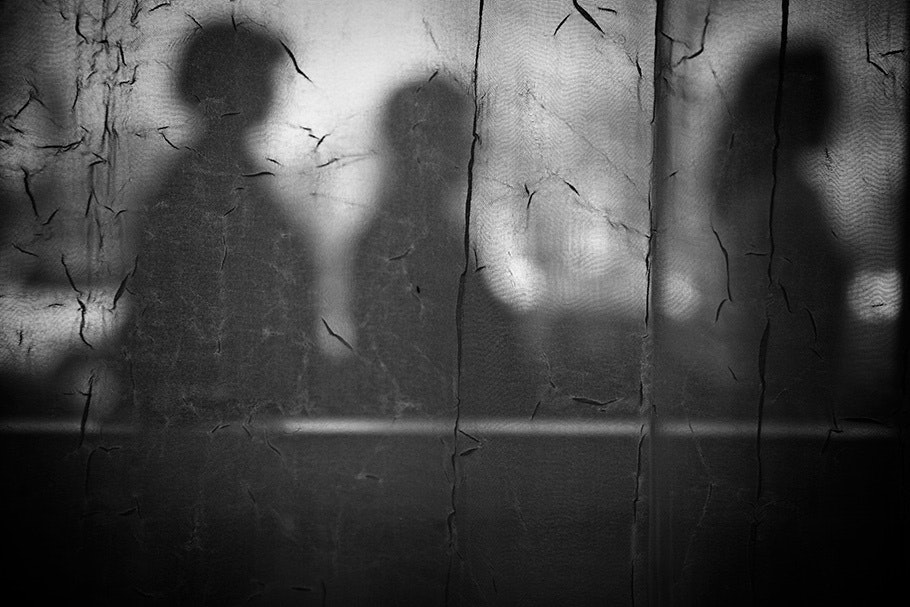 Shadows of three people on a wall.