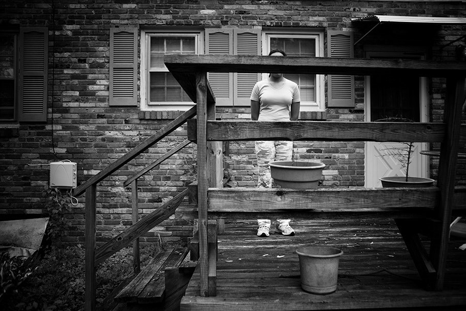 Person posed standing behind the railing of a deck.